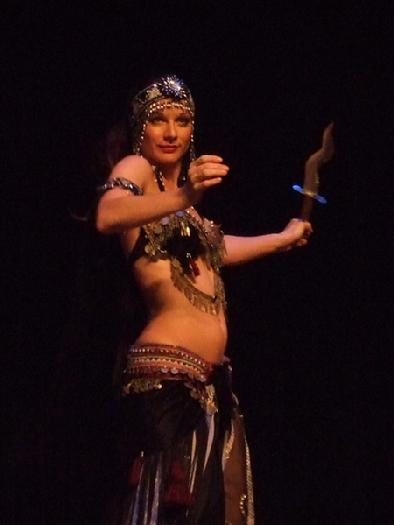 Melina performs a breath taking belly dance while balancing a sword on the tip of a dagger 130