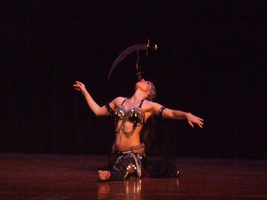 Melina performs a breath taking belly dance while balancing a sword on the tip of a dagger 144