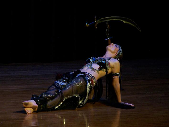 Melina performs a breath taking belly dance while balancing a sword on the tip of a dagger 185